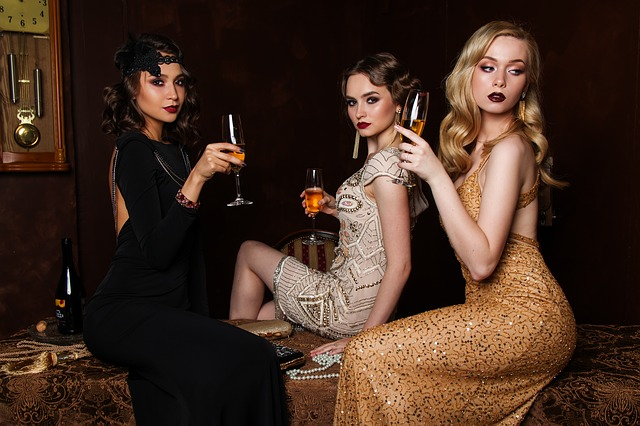tři ženy v luxusních šatech s vínem v ruce
